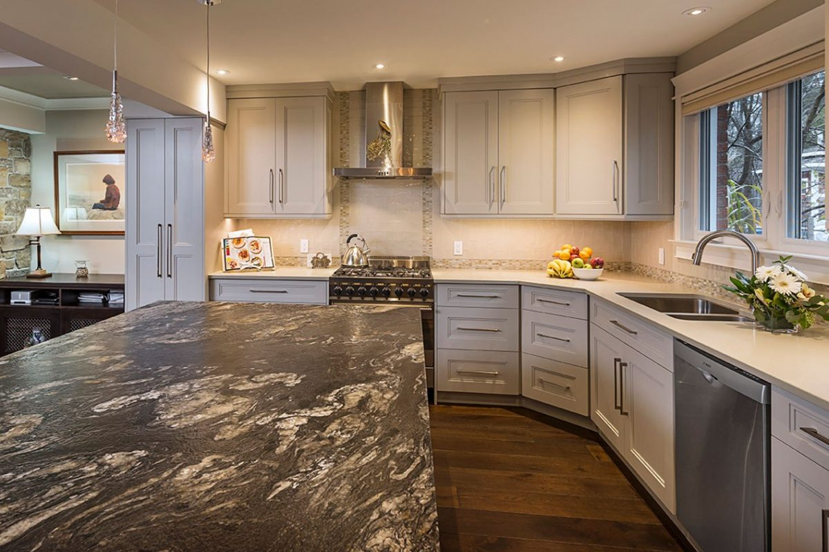 Brightly lit kitchen with granite countertop island and white cabinetry